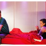 The stage is set like a bedroom with red walls and red bed sheets. A woman sits up in bed looking at a man who is sat on the foot of the bed. He looks back at her. They are both holding glasses of red wine. Both are young, white and have dark hair.