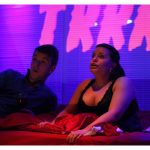 The stage is lit in a low purple glow. A young white man and a young white woman lay on a bed looking forward. The man looks taken aback