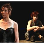 A young white actress with short red hair sits on the floor with her knees brought up to her chest. She looks on at another actress in the foreground. This actress appears to be older with curly dark hair that is tied back. She is wearing a white dress with a large black corset.