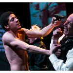 A topless man holds a gun to another actors head who is cowering. The man holding the gun is young, appears to be black and has short afro hair. The other actor is a much older white man with receding white hair. He is wearing a white shirt and a black waistcoat.