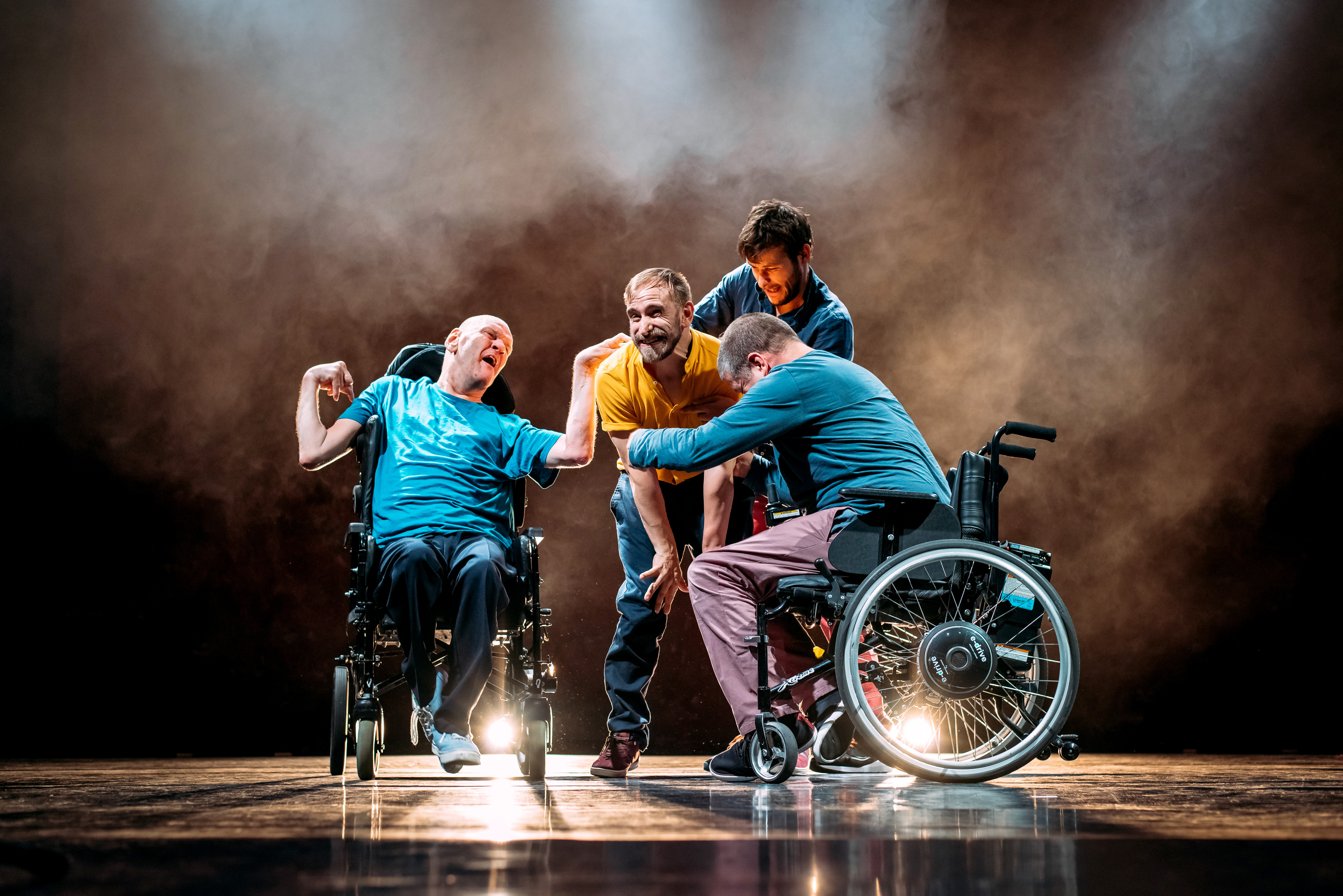 Four male performers clustered on a slightly smokey looking stage. Two of them are in wheelchairs, the other two are standing. Their ages appear to range from young to middle aged and they are dressed in various coloured shirts and jeans. They all appear to be reaching out to grab a man in a yellow T shirt who is standing in the middle of them all.