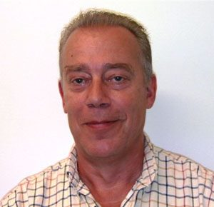 A photo of Simon Hodgson. He is a white man who appear to be in his late 40s. He has short, sparse dark blonde hair and is wearing a yellow checked shirt.