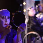 A man sits holding a mirror while putting on drag make up.