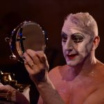 An actor in drag makeup stares at himself in a mirror.
