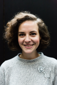 A photo of Cara Ballingall. She has short, curly brown hair and is smiling.