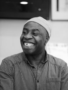 A black and white photo of Tayo Akinbode. He has a big smile and is wearing a beanie.