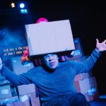 A woman places a cardboard box on a man in a wheelchairs head. He has his arms out wide and his tongue is stuck out. He is appears to be in his 30s and is wearing a blue jumper and blue trousers.