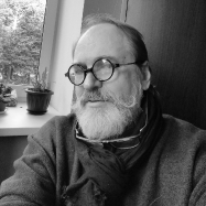 A black and white photo of Victor Nikonenko. he has a long white beard and thin wire framed round glasses.