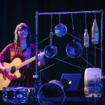 A young woman in a red checkered shirt stands playing guitar. In front of her there is a small drum, and next to that is a metal frame that has cooking pots and empty bottles hanging from it.