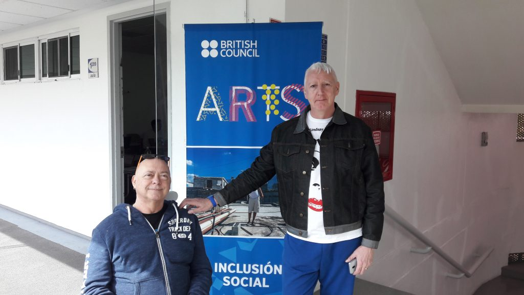 A photograph of Garry Robson and Kinny Gardner. They are in front of a banner that says 'British Council: Arts'. Garry is a white, middle aged bald man in a wheelchair. He has a pair of sunglasses on his head and is wearing a blue zipped up hoodie. Kerry also appears to be white and middle aged. He has short white hair. He is wearing blue trousers, a white T shirt with a face printed on it and a dark blue denim jacket.