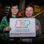 Two women smile to the camera holding a sign with the Birds of Paradise logo with '25 years' written inside it. Underneath this it says #HappyBirthdayBOP. Both women appear to be in their 30s, they are both white. One has long dark hair, while the other has short mousey brown hair.