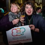 Two people hold up their wine glasses while holding up a sign together. The sign has the Birds of Paradise logo with '25 years' written inside it. Underneath this it says #HappyBirthdayBOP. The person on the left is a white woman who looks in her 30s, she has a blonde bob haircut, large glasses and is wearing a scarf. Next to her there is a white person with curly brown hair, they are wearing a black top, with a blue jacket over it, a chunky necklace and red lipstick.