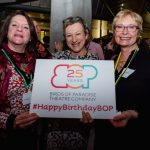 Three women smile holding a sign with the Birds of Paradise logo with '25 years' written inside it. Underneath this it says #HappyBirthdayBOP. They are all white and middle aged. The woman on the left has medium length brown hair and is wearing a long sleeved red top with white flowers on it. The woman in the middle has swept back blonde hair and is wearing a black and white damask patterned dress. The woman on the right, has short blonde hair, glasses and is wearing a black dress.