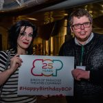 Two people, a man and a woman smile holding a sign with the Birds of Paradise logo with '25 years' written inside it. Underneath this it says #HappyBirthdayBOP. The woman appears to be in her 30s, she has tousled black hair and dark makeup. She is wearing a black and white striped top. The man appears to be in his late 20s. He has short brown hair, glasses and is wearing a black jumper.