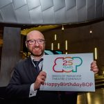 A man smiles holding a sign with the Birds of Paradise logo with '25 years' written inside it. Underneath this it says #HappyBirthdayBOP. The man appears to be in his late 40s, white, he is bald with a brown beard, is wearing glasses and a grey three piece suit.