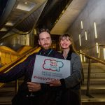 Two people, a man and a woman pose on the stairs with a sign with the Birds of Paradise logo with '25 years' written inside it. Underneath this it says #HappyBirthdayBOP. The man appears to be in his late 20s, he has brown hair and a short brown beard. He is wearing a patterned purple top. The woman next to him is smiling wide, she is white and also appears to be in her late 20s, she has long blonde hair and is wearing a grey coat with black accents.
