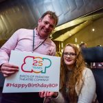 Two people, a man and a woman smile holding a sign with the Birds of Paradise logo with '25 years' written inside it. Underneath this it says #HappyBirthdayBOP. The man appears to be in his late 40s, white, with brown hair and a pink shirt. The woman next to him is sat in a wheelchair and appears to be in her early 20s/ late teens. She is white, with long wavy red hair and glasses.