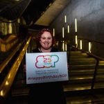 A woman smiles and holds up a sign with the Birds of Paradise logo with '25 years' written inside it. Underneath this it says #HappyBirthdayBOP. She appears to be in her early 30s, white, with curly ginger hair.