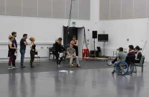Image from rehearsing a scene: In a large white and grey room with no set, one person sits in a chair while two people fuss aorund him and the rest of the cast stand in a line and watch. Watching them are Robert, Scott and EJ - who are the creative team.