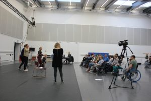 Side view of the sharing: On the right, the cast go through the scenes they have rehearsed - there are no costumes or set and their scripts are scattered about close to hand, on the right are two rows of an invited audience from National Theatre of Scotland.