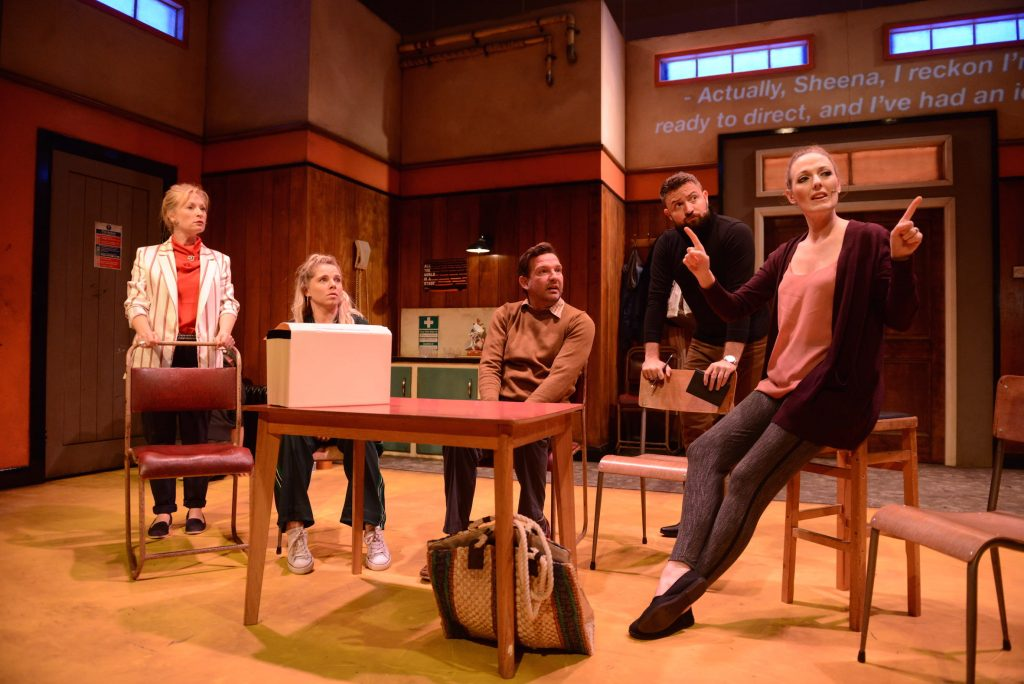 5 actors are sat around a desk on stage. They all look to an actor on the right who appears to be explaining something.