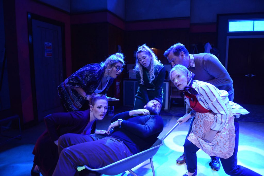 6 actors huddle at the front of the stage which is lit blue. One of the actors lies in a wheelbarrow which the others are pushing.