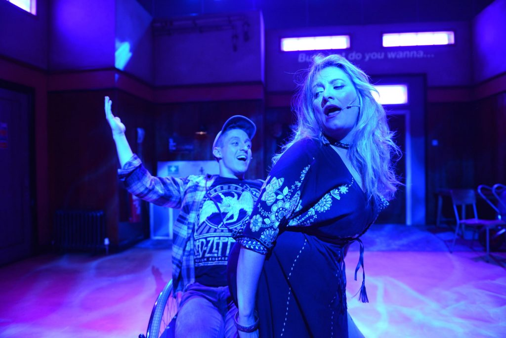 An actor with a cap on sits in a wheelchair. A woman is crouching in his lap. They both appear to be singing.