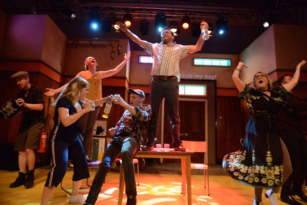 7 actors are on stage dancing and singing. 2 of them are standing on chairs with their arms in the air and two of them are toasting over a drink.