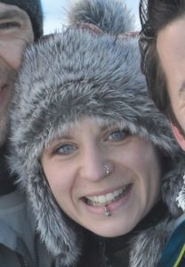 A photo of Katy Lonsdale. She has blue eyes, a lip piercing and a nose piercing and is wearing a fluffy grey hat.