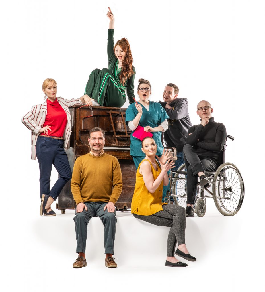 A poster for the show. It features seven cast members, they are all gathered around a large piano, with one woman sat on top of it. They are all in modern clothes and smiling at the camera