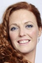 A photo of Natalie MacDonald. She has curly ginger hair, blue eyes and a big smile.