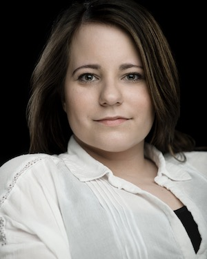 A headshot of Amy Conachan. She is a white woman who appears to be in her early 30s. She has long dark hair and is wearing a white shirt.