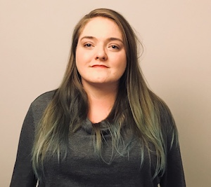 A photo of Jai Hutchison. She is a white woman who appears to be in her mid 20s. She has very long dark hair and is wearing a long sleeved grey top.