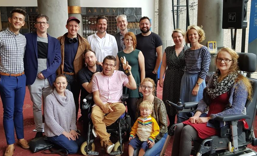 Various members of the cast and crew for My Left / Right Foot clump together in the foyer of Festival Theatre, Robert holds the Herald Angel ward up into the air. Everyone is smiling.