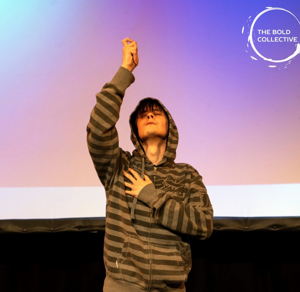 A performer- his hood is up, his eyes are closed. One hand is on his heart, his other hand reaches upwards- hopeful.