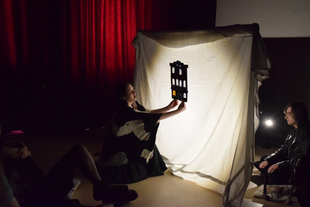 The silhouette of a house with many windows, set against a white backdrop, with a light shining through. Emily is kneeling on the ground, holding up the house- demonstrating some shadow puppetry to a group.