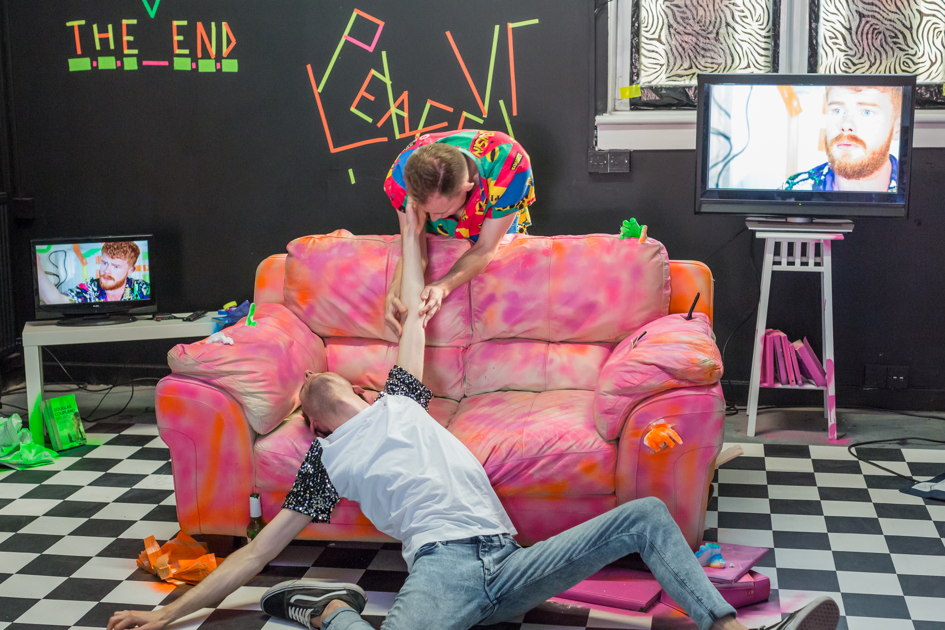 A scene from the show, a young man is sprawled on the floor and another young man leans over a pink sofa pulling up the other man by his arm. The floor is made up of black and white squares. The walls are black and with bright orange and green tape in some parts. In the top left corner, this tape spells out 'the end'. There are two small screens on either side of the sofa, both show a different close up of a young man with ginger hair.