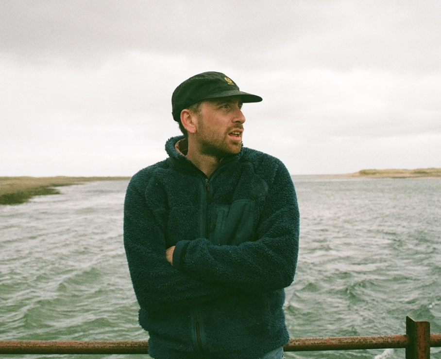 Image of the devastatingly handsome Callum. He is wearing a fluffy blue fleece and a black cap and is staring off into the distance while standing on a bridge with a murky estuary behind him.