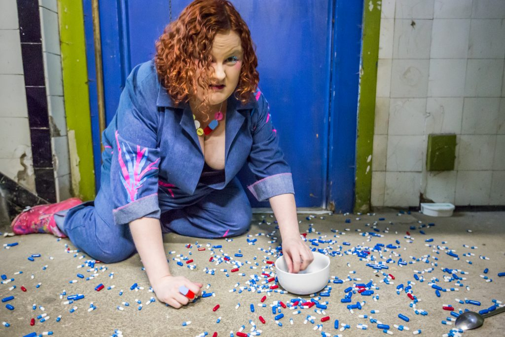 Wearing a blue boiler suit, Heather is on her hands and knees in what looks like a run down public toilet, the floor is covered in lots of pills and she is trying to collect them up into a white ceramic bowl.