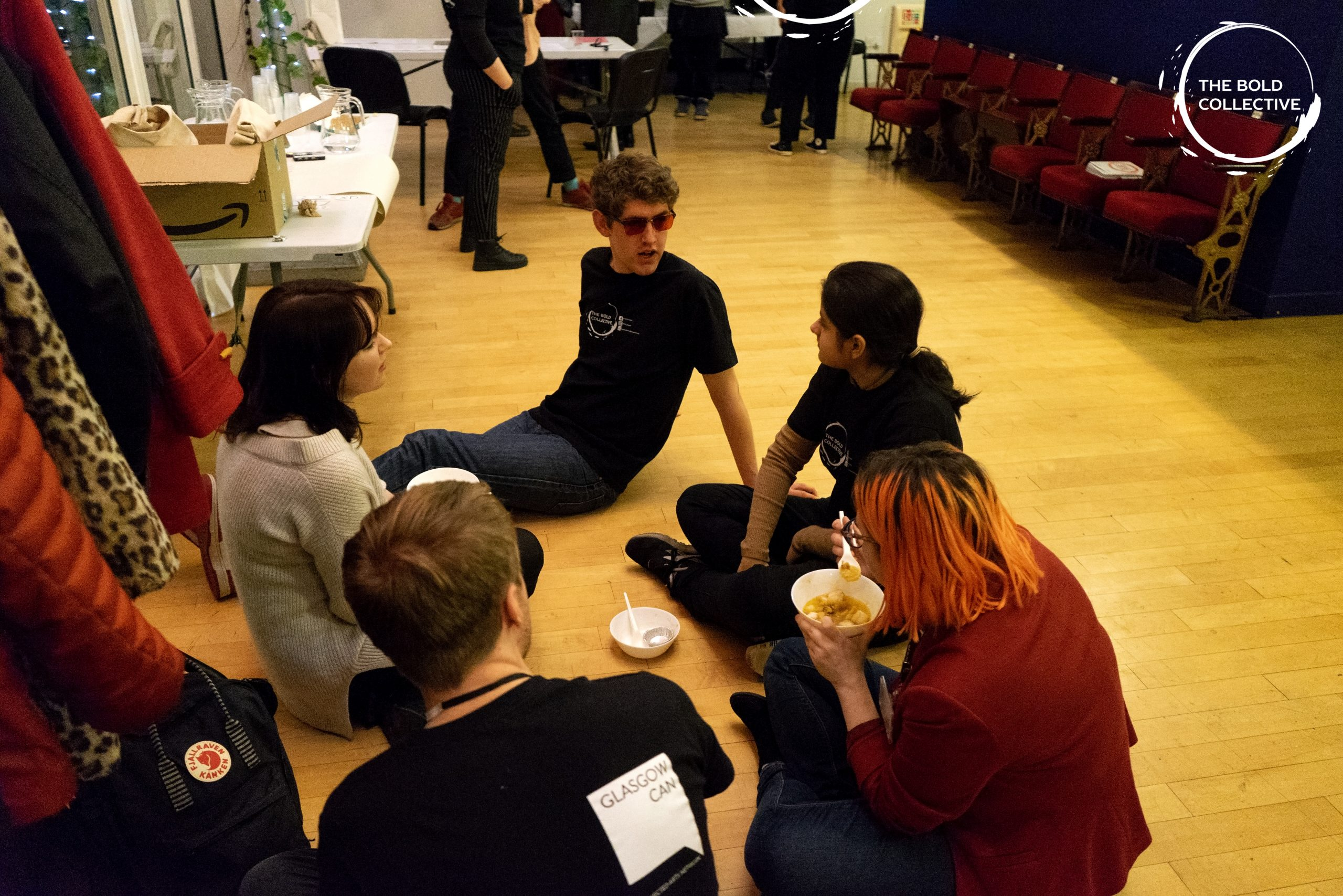 A group of five young people sit on the floor- relaxing, eating food and chatting.