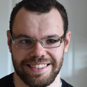 Photograph of Gavin Yule. Gavin has very dark brown curly (but tightly cropped) hair. Gavin has a beard which is very short and neatly trimmed. He has dark brown eyes behind square-rimmed glasses, and is smiling with his lovely white teeth.
