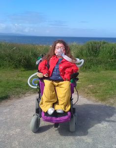 Photograph of Karis Williamson. Karis has pale skin with a rosy complexion and she has long brown wavy hair. She wears glasses, and you can't tell what colour her eyes are in this photograph. Karis is wearing a ventilation mask, which is attached to her power chair. She wears block colours: a bright red denim jacket, mustard yellow cullotes and a blue t-shirt.