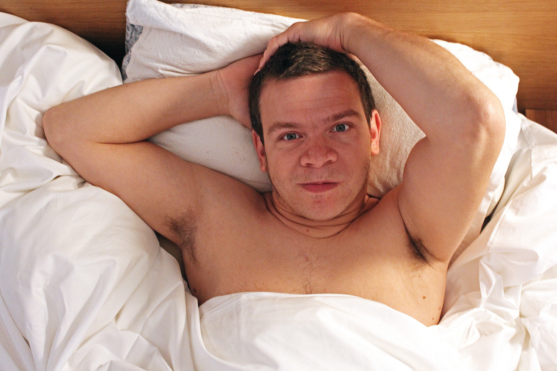 Robert, a white middle aged man, lies back in bed facing the camera. He has the white bed covers pulled up over his nipples and his hands back behind his head. He looks smoulderingly at the camera.
