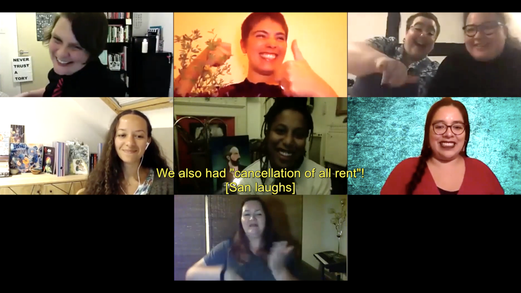 "Still from 'A Wake' discussion hosted on Zoom, with eight people visible in seven squares. A yellow caption reads: ""We also had 'cancellation of all rent! [San laughs]"" Left-Right, Top Row: San Alland is white with short brown hair, they wear a black shirt and black and red striped tie, and they're laughing; Emilia Beatriz is Puerto Rican American with very short brown hair and a black top, they are sitting next to a plant and smiling large while giving a double thumbs-up. Emma Webster-Mockett is a white woman with very short brown hair, glasses and a septum piercing. She gestures excitedly to the camera while sitting next to a smiling Bea Webster, who is Scottish-Thai with straight shoulder-length dark hair, brown eyes and glasses. Left-Right, Middle Row: Jeda Pearl sits in front of a bookshelf wearing headphones and smiling, she has long, brown curly-frizzy hair, bronze-brown skin and brown eyes; Lake Montgomery is African-American with chest-length finger-thick dreadlocks, brown eyes and no makeup, she laughs in front of a portrait painting and a lit candle; Etzali is a nonbinary latinx femme, they have brown eyes, hoop nose piercings, long fluffy black hair and glasses, and sit smiling in front of a bright turquoise backdrop. Bottom Row: Yvonne Strain is a white woman with shoulder-length wavy brown hair, she is interpreting into British Sign Language."