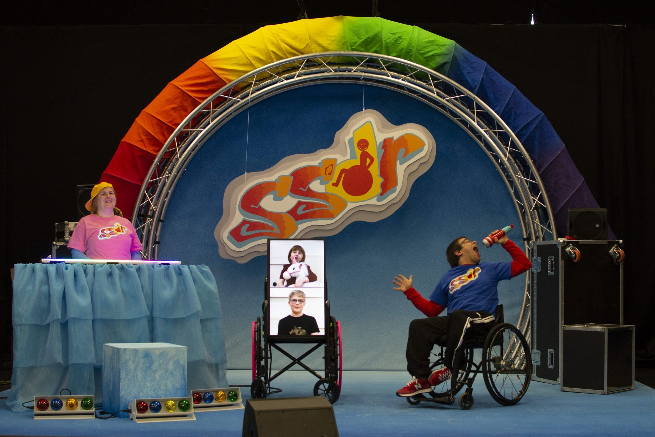 The woman is standing on the left behind the musical equipment that is covered in a blue sheet. She is smiling. On the right, the man in the wheelchair is holding a microphone with his mouth wide open and his head thrown back. In the middle of them, there is a screen on wheels with two people on it against a white background. One of these people appears to be holding a white toy pony.