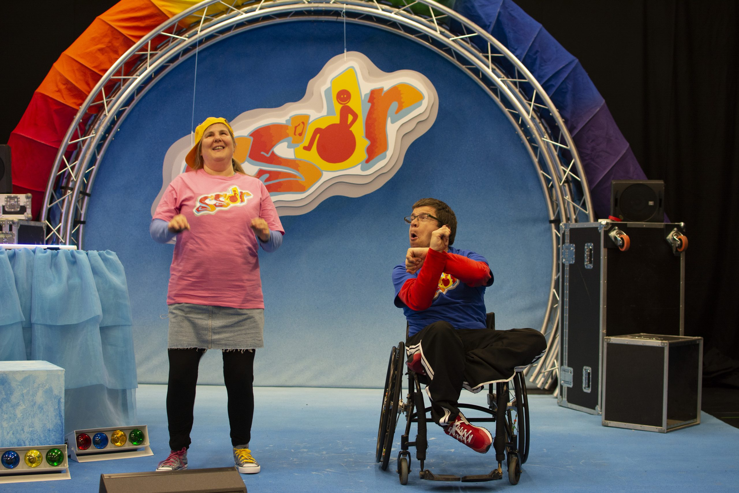Sally and Robert are positioned at the front of the stage. Robert, on the right, has his arms positioned in an X as he looks over at Sally. Sally, on the left, is smiling and has her hands lifted at her sides as if mid gesture.