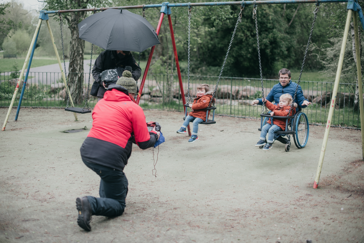 A swing set outside. There are two very young toddlers, each in their own swing with behind pushing them. In front of them there is a man on one knee holding a camera filming them. Everyone is wearing thick winter coats.