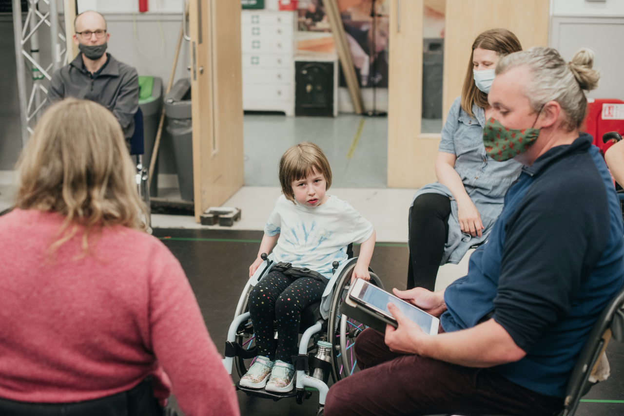 People sit around a rehearsal room. In the foreground is Oona in her chair, in the background is Joe, holding an iPad and Sal facing Oona with her back to the camera.