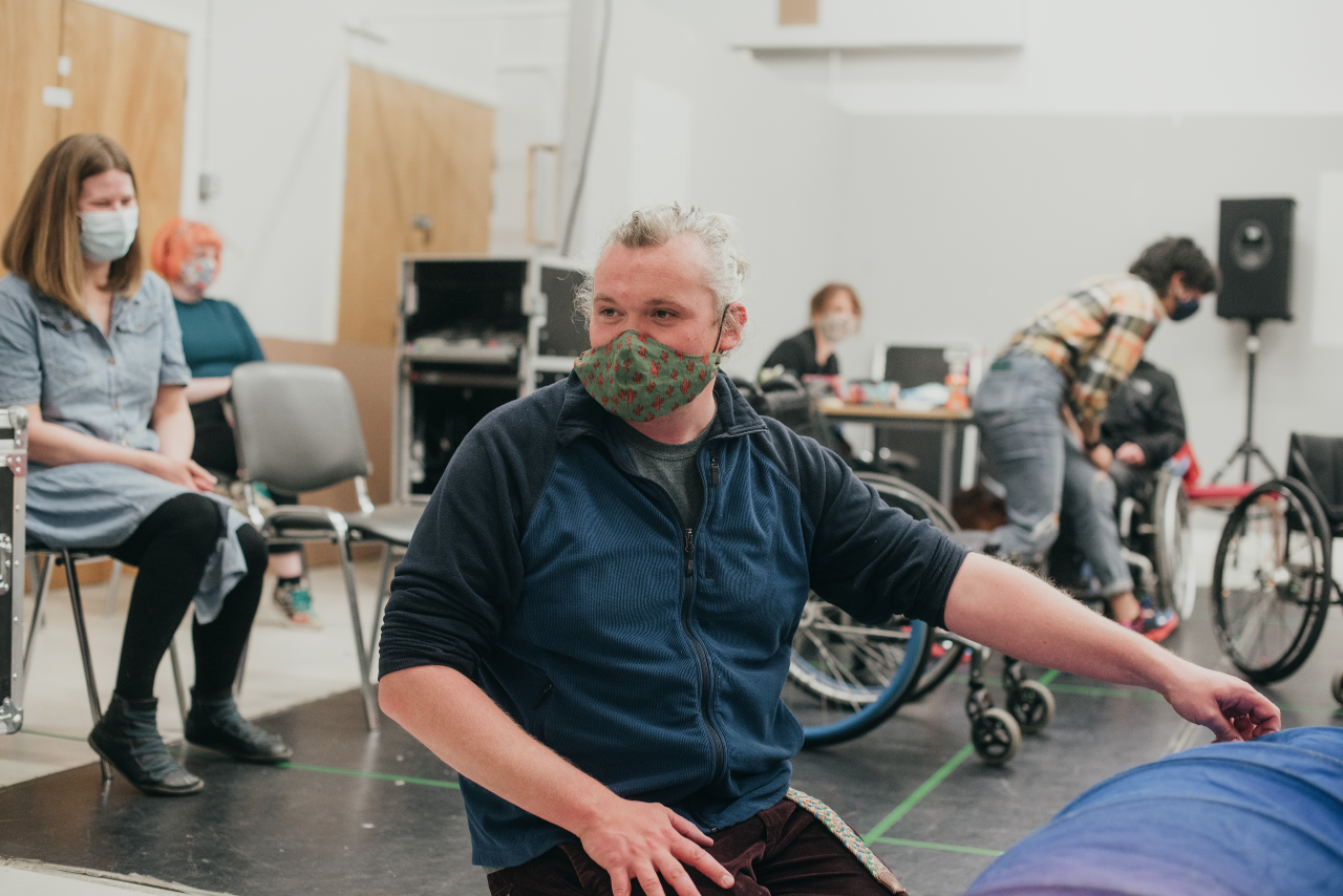 A rehearsal room full of people spread out on chairs. The camera is focused on Joe (the director) middle aged man with long grey hair that is pulled back. He is wearing a green patterned mask and is looking at something off camera. He has one hand reached out and is touching something large and blue on the floor.