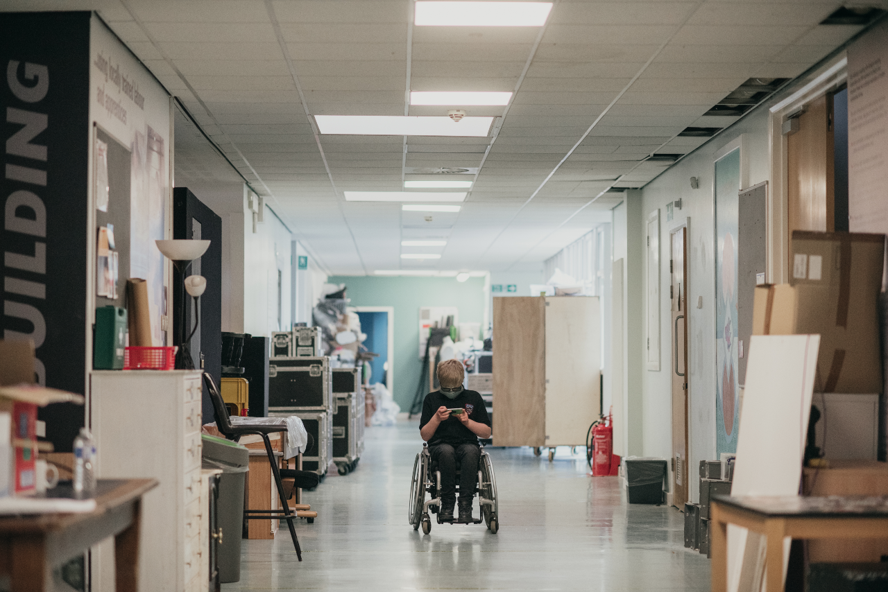 A shot of a cluttered corridor. There are various things lining it, such as: lights, cardboard boxes and pieces of furniture. In the middle there is Ollie in a wheelchair looking down at their phone.